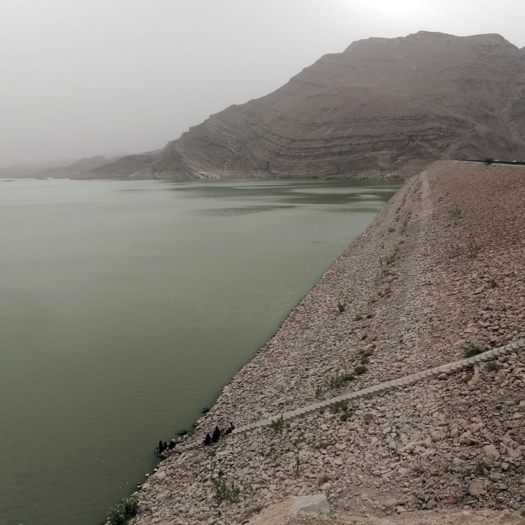 Women stand near the water's edge at the Marib Dam in Yemen on July 30, 2018. (AP Photo/Nariman El-Mofty)