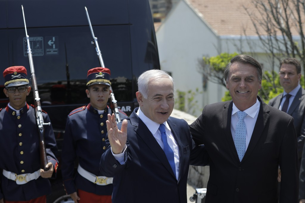 Israeli Prime Minister Benjamin Netanyahu waves as he is received by Brazil's President-elect Jair Bolsonaro at the military base Fort Copacabana, in ...