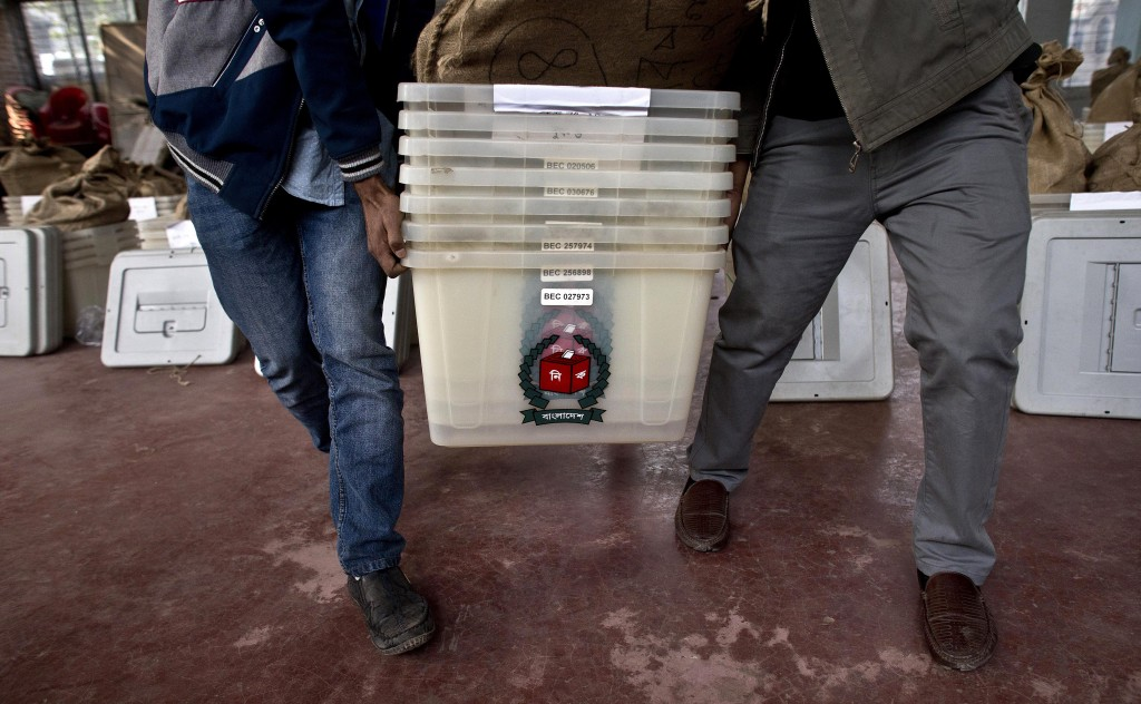 Bangladeshi election officials carry voting material at a distribution center before being transported to different polling stations on the eve of the...