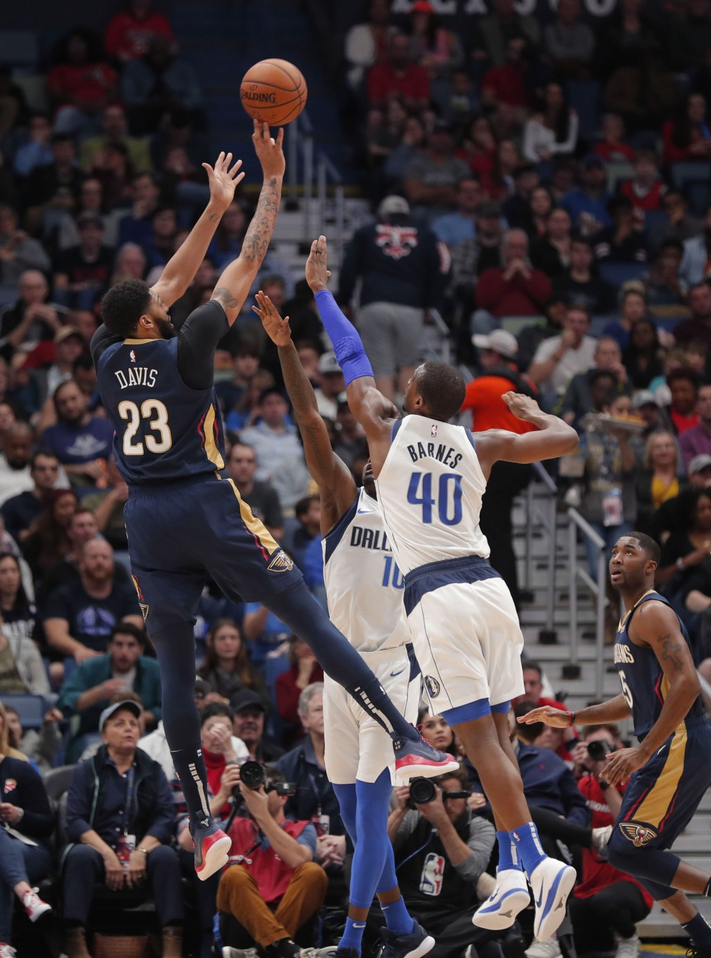 New Orleans Pelicans forward Anthony Davis (23) shoots as Dallas Mavericks forwards Dorian Finney-Smith (10) and Harrison Barnes (40) defend during th...