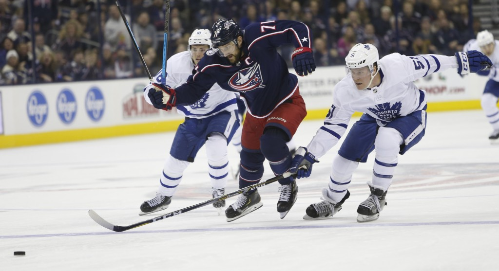 Columbus Blue Jackets' Nick Foligno, center, carries the puck across the blue line between Toronto Maple Leafs' Andreas Johnsson, left, of Sweden, and...