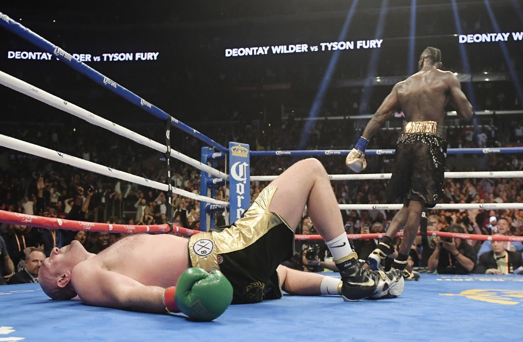 FIEL - In this Saturday, Dec. 1, 2018, file photo, Tyson Fury, of England, lies on the canvas after being knocked down by Deontay Wilder during the 12...