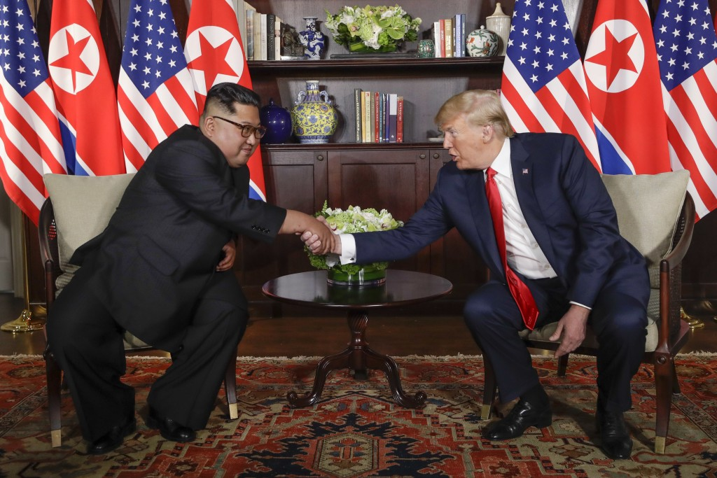 In this Tuesday, June 12, 2018, file photo, North Korea leader Kim Jong Un, left, and U.S. President Donald Trump shake hands during their first meeti...