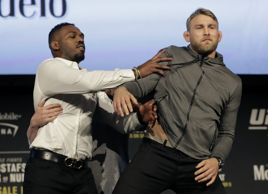 FILE - In this Nov. 2, 2018, file photo, Jon Jones, left, pushes Alexander Gustafsson out of the way during a news conference about their light heavyw...
