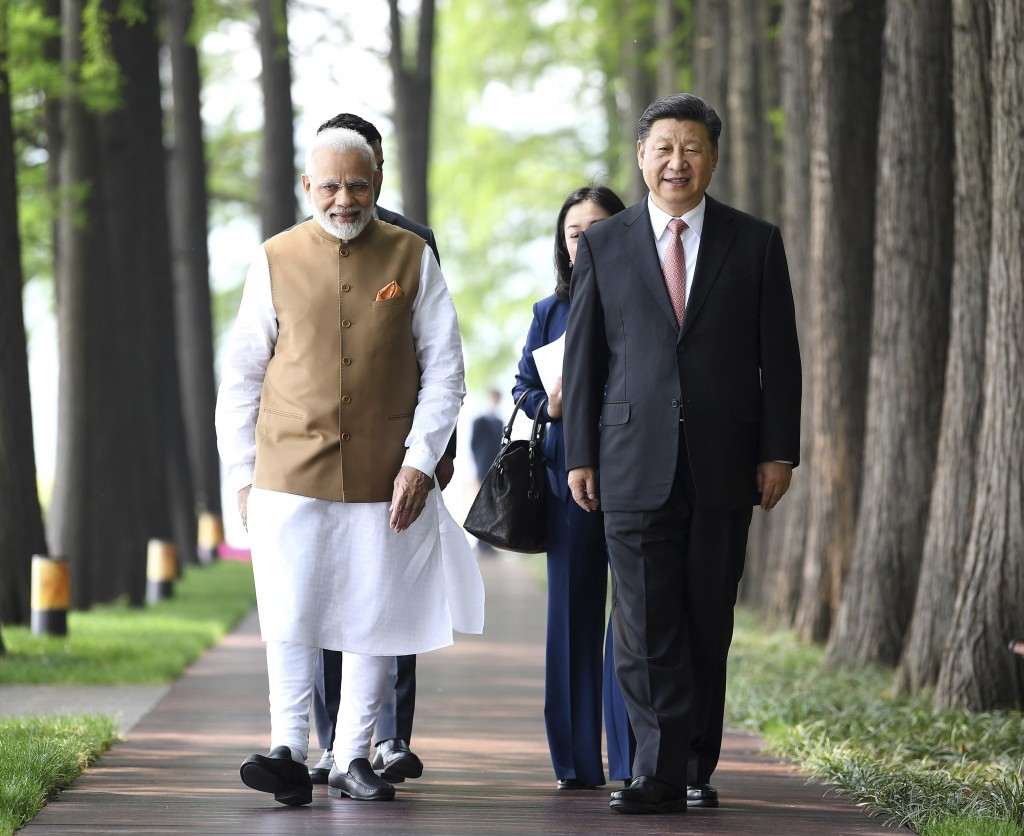 In this April 28, 2018, file photo released by China's Xinhua News Agency, Indian Prime Minister Narendra Modi, left, and Chinese President Xi Jinping...
