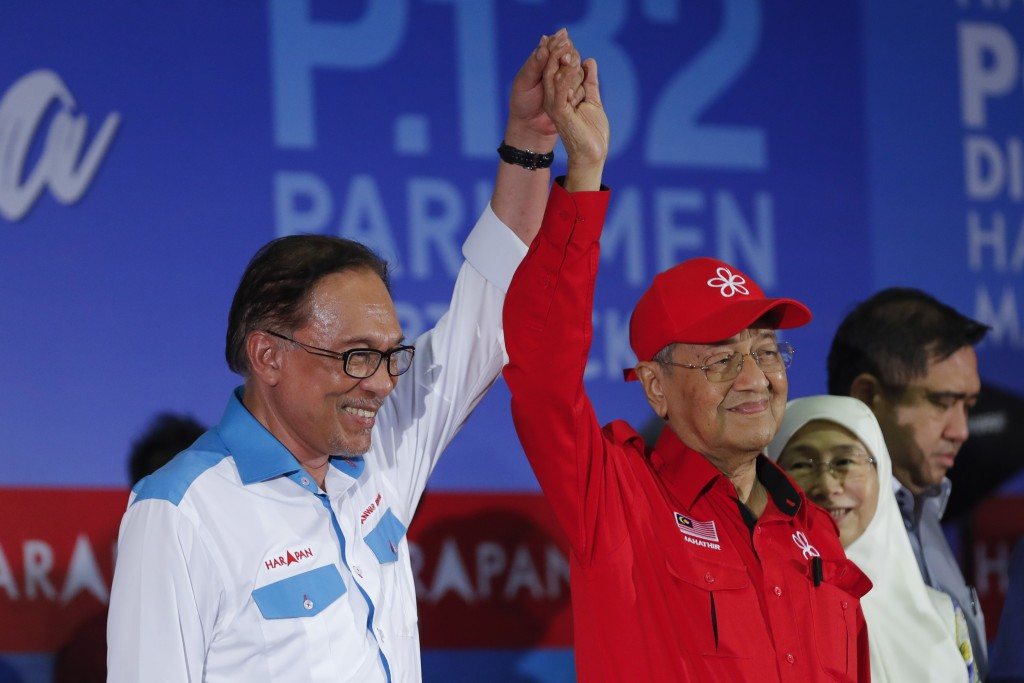 In this Oct. 8, 2018, file photo, Malaysia's Prime Minister Mahathir Mohamad, right, raises the hand of Malaysia's reform icon Anwar Ibrahim during a ...