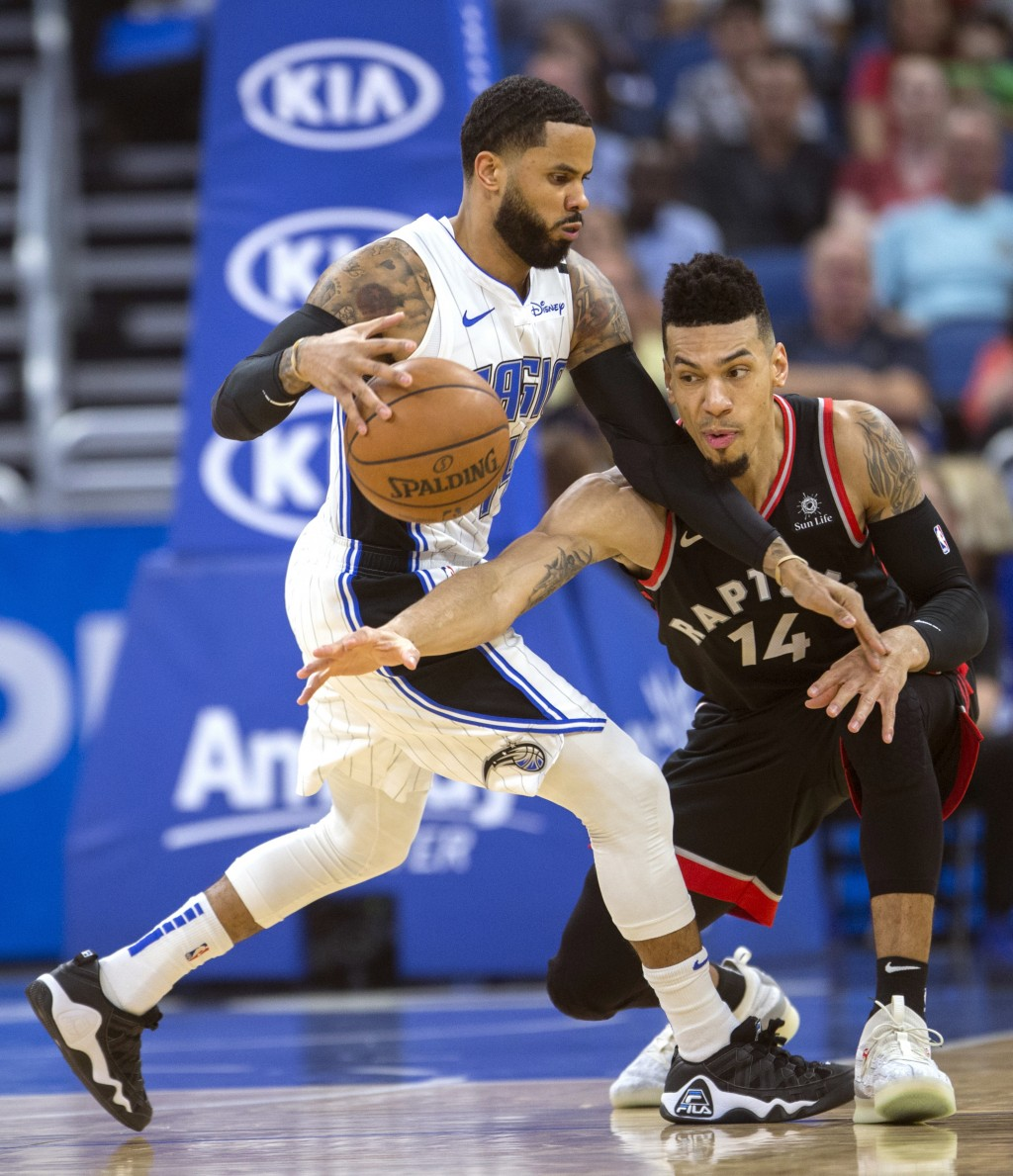 Orlando Magic guard D.J. Augustin (14) dribbles through Toronto Raptors guard Danny Green (14) during the first half of an NBA basketball game in Orla...