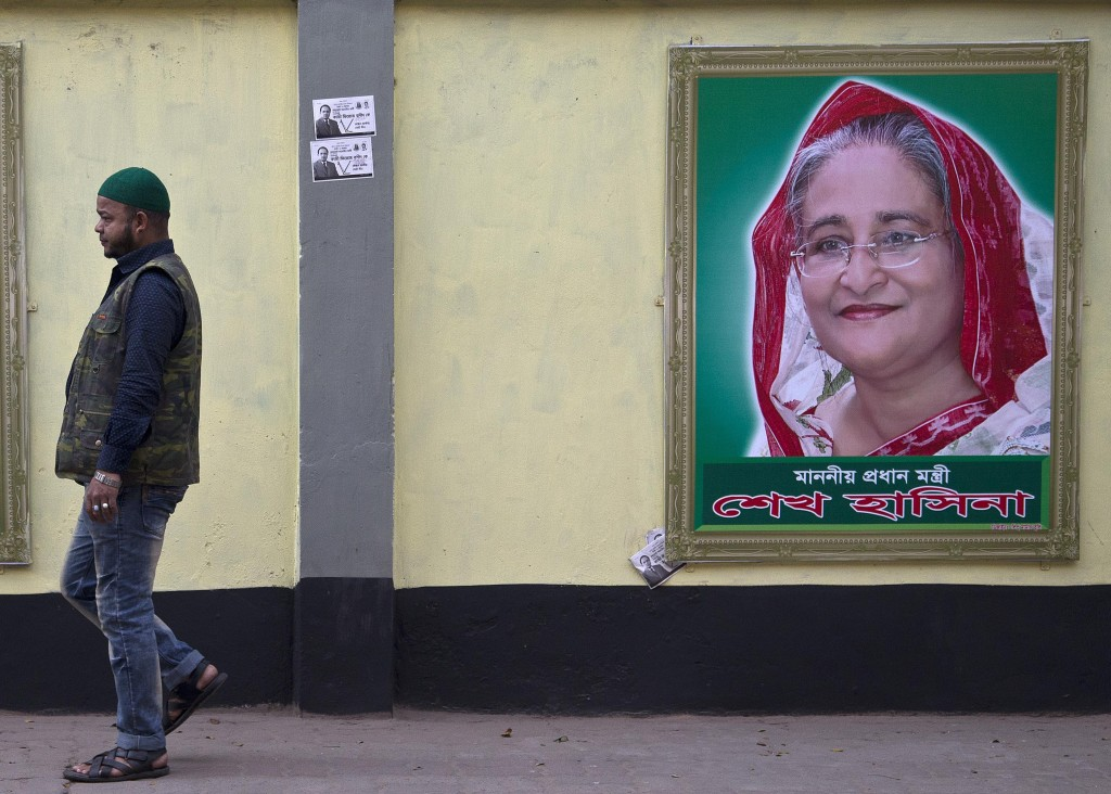 A man walks past a portrait of Bangladesh Prime Minister Sheikh Hasina on the eve of general elections in Dhaka, Bangladesh, Saturday, Dec. 29, 2018. ...