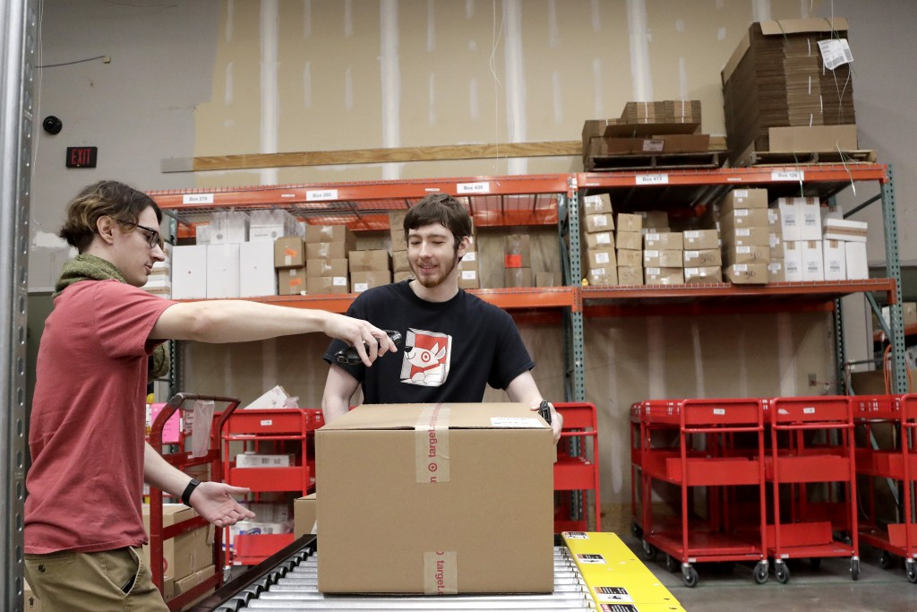 FILE - In this Nov. 16, 2018, file photo, Target employees sort boxed items from online orders to be shipped out to customers at at a Target store in ...