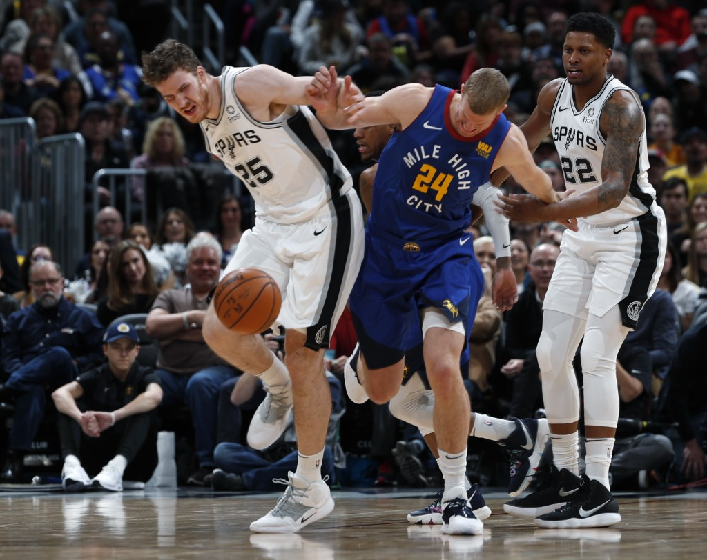 San Antonio Spurs center Jakob Poeltl, left, fights for control of a loose ball with Denver Nuggets forward Mason Plumlee in the first half of an NBA ...