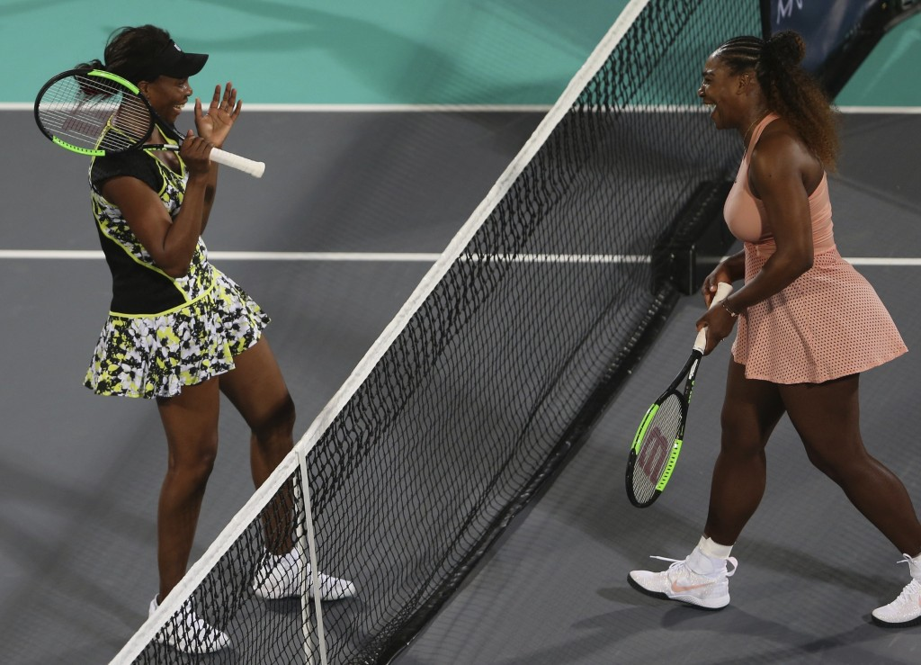 Venus Williams, left, from the U.S., celebrates after defeating her sister, Serena, in a match during the opening day of the Mubadala World Tennis Cha...