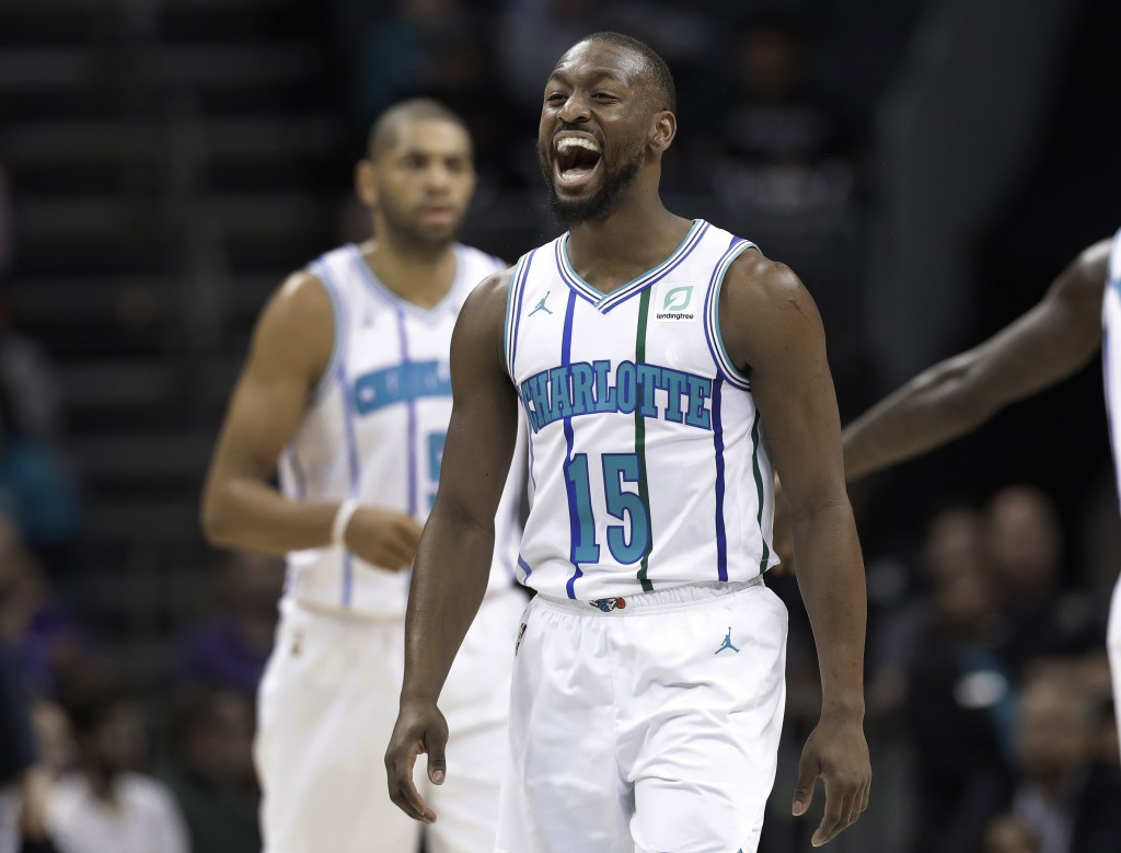 Charlotte Hornets' Kemba Walker (15) celebrates after making a basket against the Brooklyn Nets during the first half of an NBA basketball game in Cha...