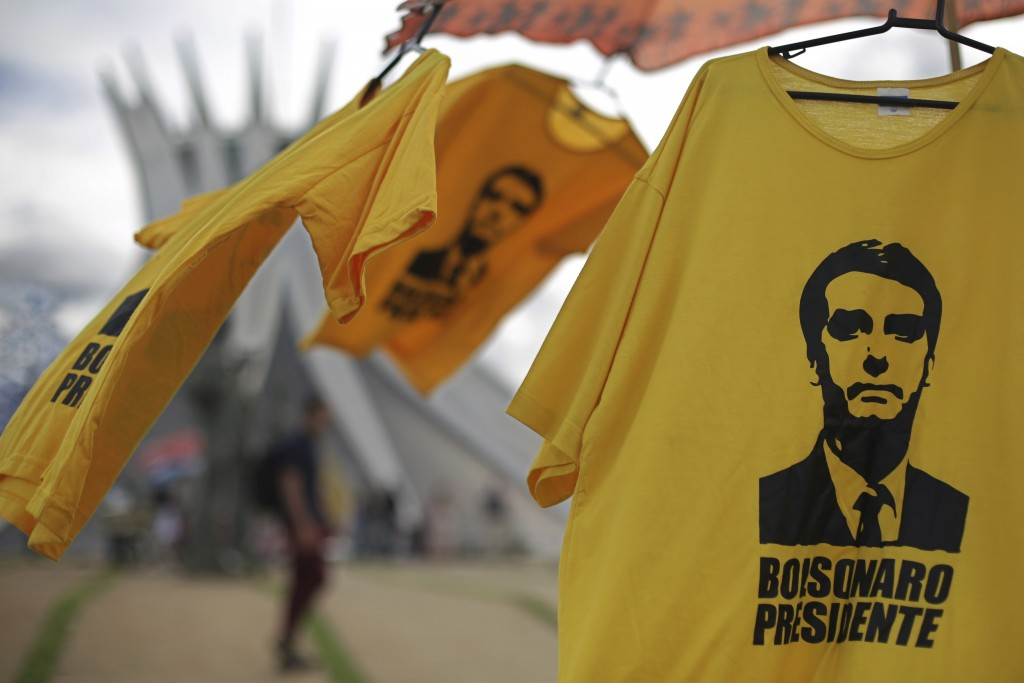 Shirts with the image of Brazil's President-elect Jair Bolsonaro are displayed for sale in front of the Cathedral, in Brasilia, Brazil, Friday, Dec. 2...