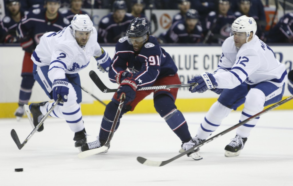 Columbus Blue Jackets' Anthony Duclair, center, carries the puck up ice between Toronto Maple Leafs' Ron Hainsey, left, and Patrick Marleau during the...
