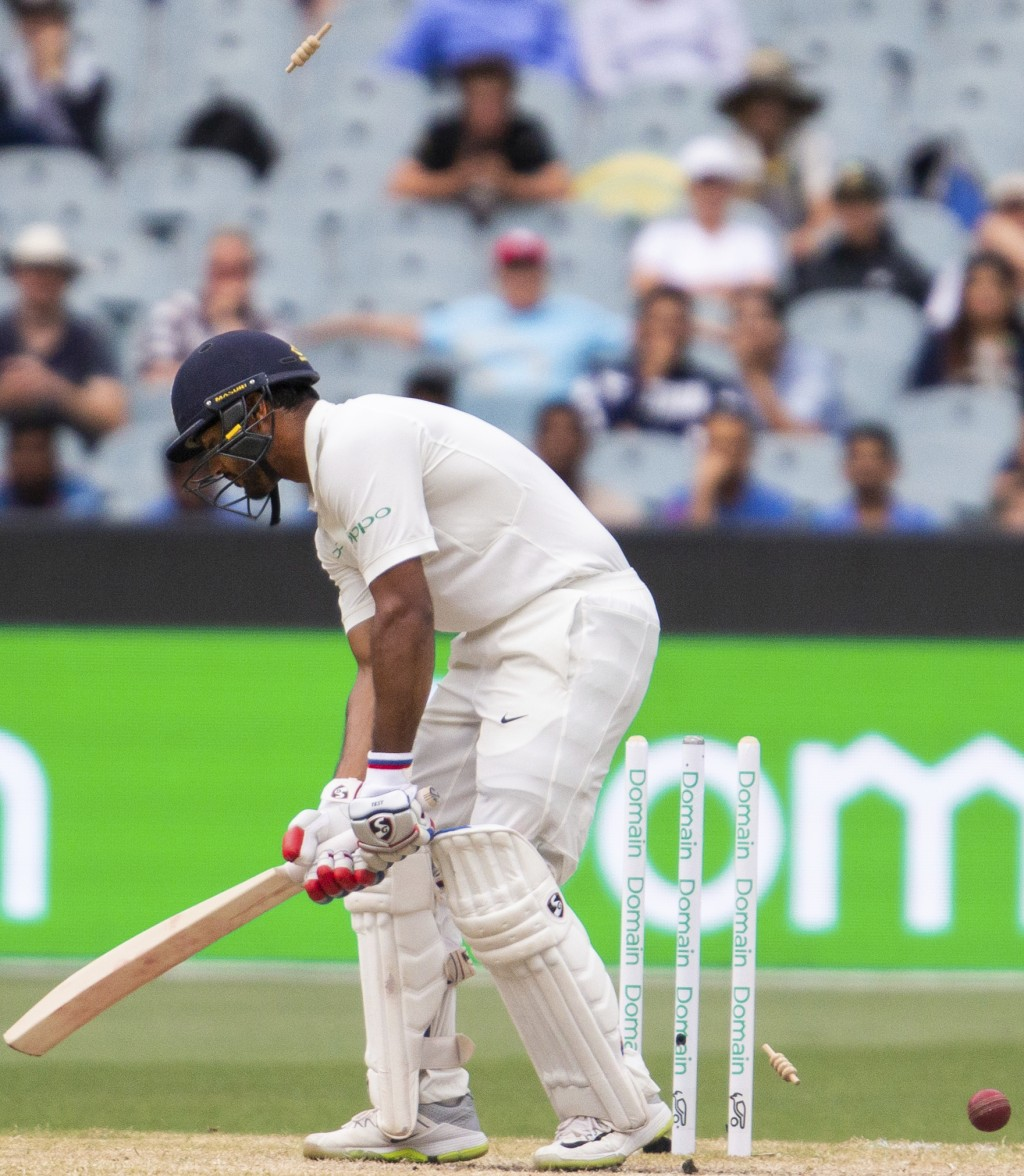 India's Mayank Agarwal gets bowled by Pat Cummins during play on day four of the third cricket test between India and Australia in Melbourne, Australi...
