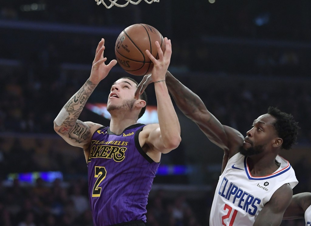 Los Angeles Lakers guard Lonzo Ball, left, shoots as Los Angeles Clippers guard Patrick Beverley defends during the first half of an NBA basketball ga...