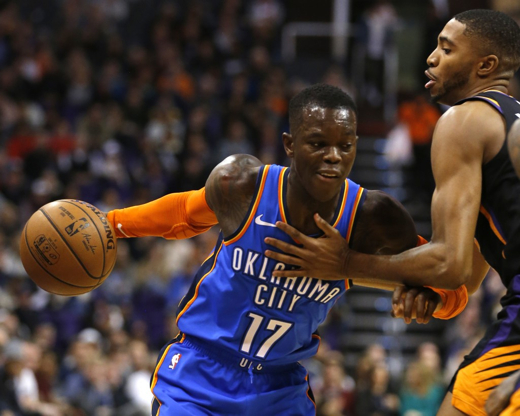 Oklahoma City Thunder guard Dennis Schroder (17) drives against Phoenix Suns guard Troy Daniels in the first half during an NBA basketball game, Frida...