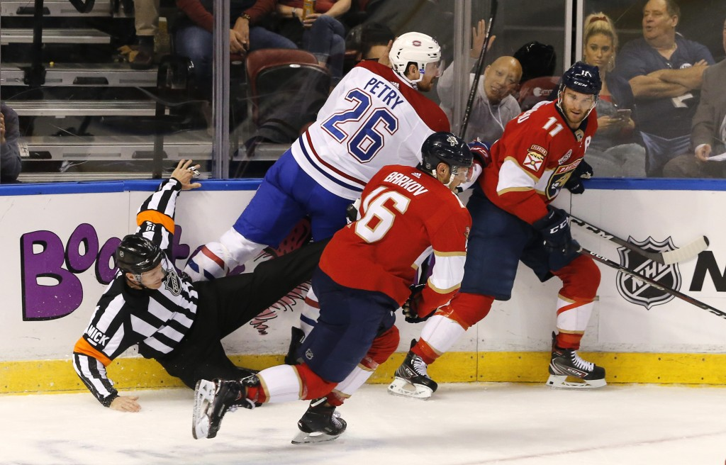 Referee Gord Dwyer, left, goes to the ice after being caught between Montreal Canadiens defenseman Jeff Petry (26) and Florida Panthers center Aleksan...