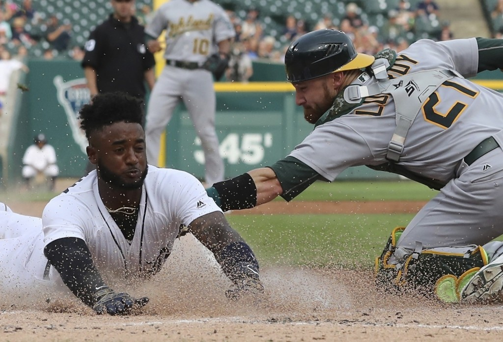 FILE - In this June 26, 2018, file photo, Detroit Tigers shortstop Niko Goodrum beats the tag of Oakland Athletics catcher Jonathan Lucroy during the ...