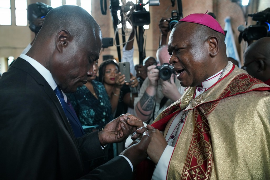 Congolese opposition presidential candidate Martin Fayulu is blessed by Msg. Fridolin Ambongo, the the newly appointed Archbishop of Kinshasa at Notre...