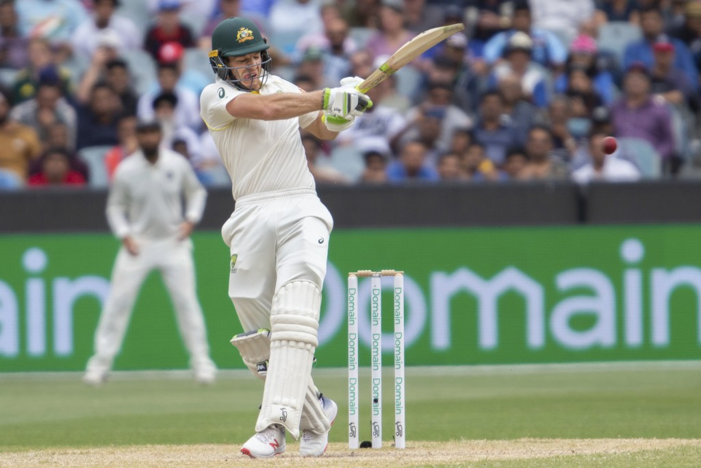 Australia's Tim Paine plays a shot during play on day four of the third cricket test between India and Australia in Melbourne, Australia, Saturday, De...
