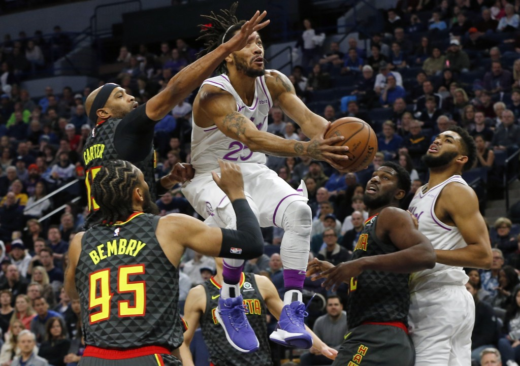 Minnesota Timberwolves' Derrick Rose, center, drives between Atlanta Hawks' Vince Carter, top left, and other defenders during the first half of an NB...