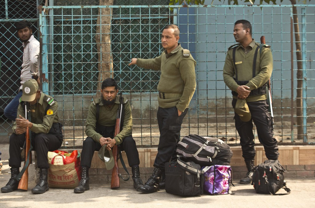 Bangladeshi police personnel with their belongings wait to accompany polling officials at a distribution center on the eve of the general elections in...