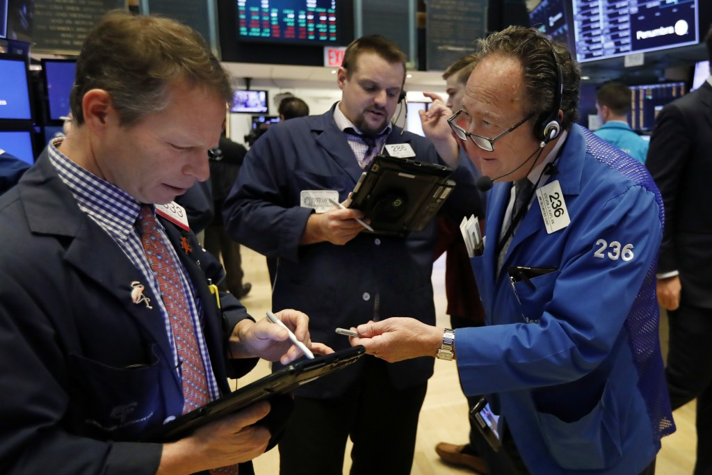 Traders Robert Charmak, Michael Milano, and Steven Kaplan, left to right, work on the floor of the New York Stock Exchange, Friday, Dec. 28, 2018. Sto...
