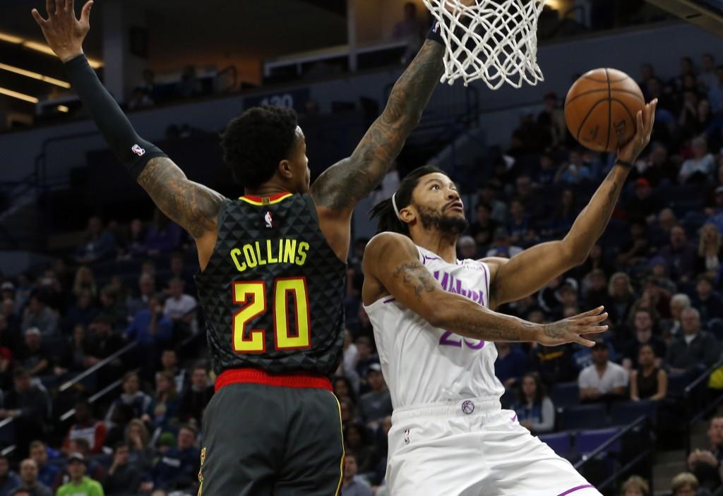 Minnesota Timberwolves' Derrick Rose, right, lays up a shot as Atlanta Hawks' John Collins defends during the first half of an NBA basketball game Fri...