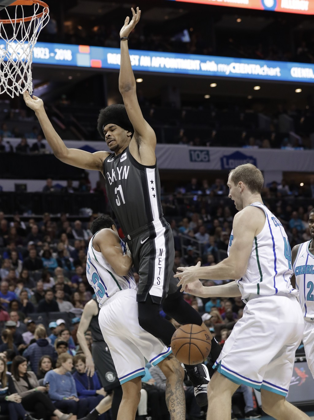 Brooklyn Nets' Jarrett Allen (31) loses the ball as he drives between Charlotte Hornets' Jeremy Lamb (3) and Cody Zeller during the first half of an N...