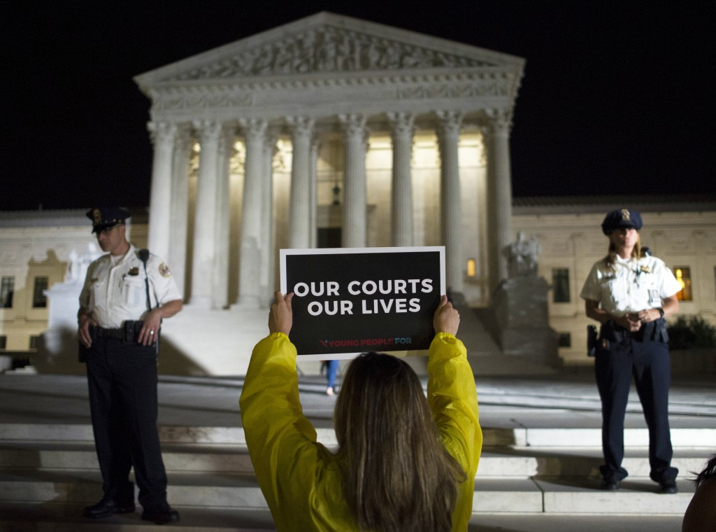 FILE - In this July 9, 2018, file photo a demonstrator protests in front of the Supreme Court in Washington. The Supreme Court term has steered clear ...