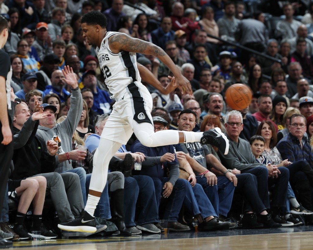 San Antonio Spurs forward Rudy Gay saves the ball from bouncing out of play as he runs into fans in the courtside seats in the first half of an NBA ba...