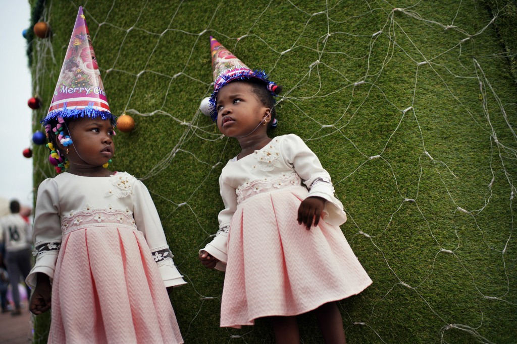 Twins pose for a photograph in Kinshasa, Congo, on Tuesday Dec. 25, 2018. People dress up and take to the parks on Christmas Day, this time five days
