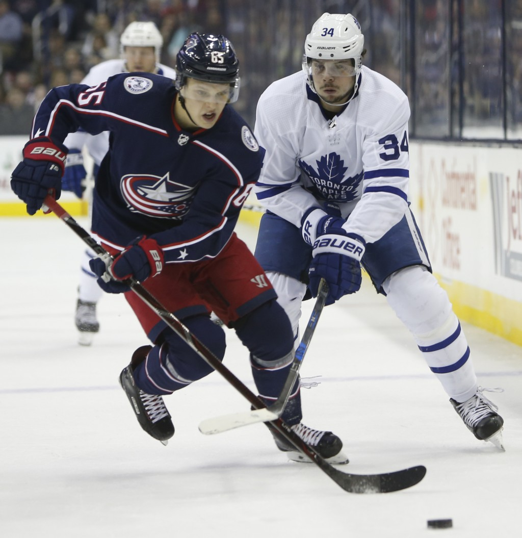 Columbus Blue Jackets' Markus Nutivaara, left, of Finland, controls the puck as Toronto Maple Leafs' Auston Matthews defends during the first period o...