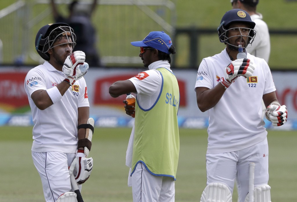 Sri Lanka's Kusal Mendis and teammate Dinesh Chandimal, right, take a drink during a break in play on day four of the second cricket test between New ...