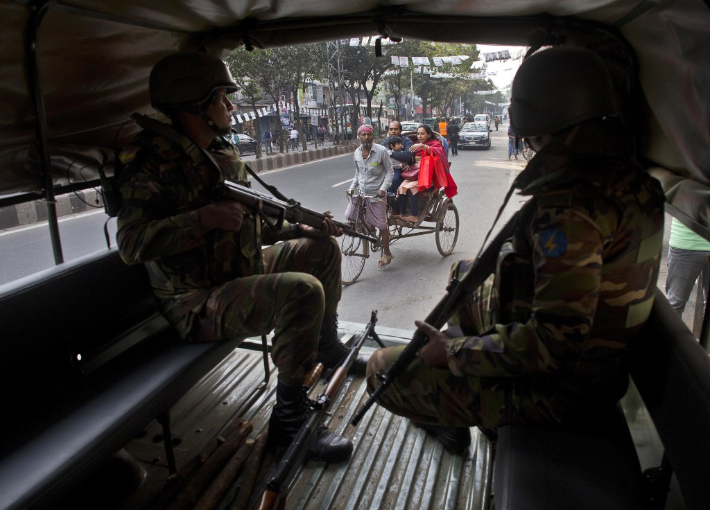 Bangladeshi army soldiers keep vigil as a rickshaw puller transports passengers on the eve of the general elections in Dhaka, Bangladesh, Saturday, De...