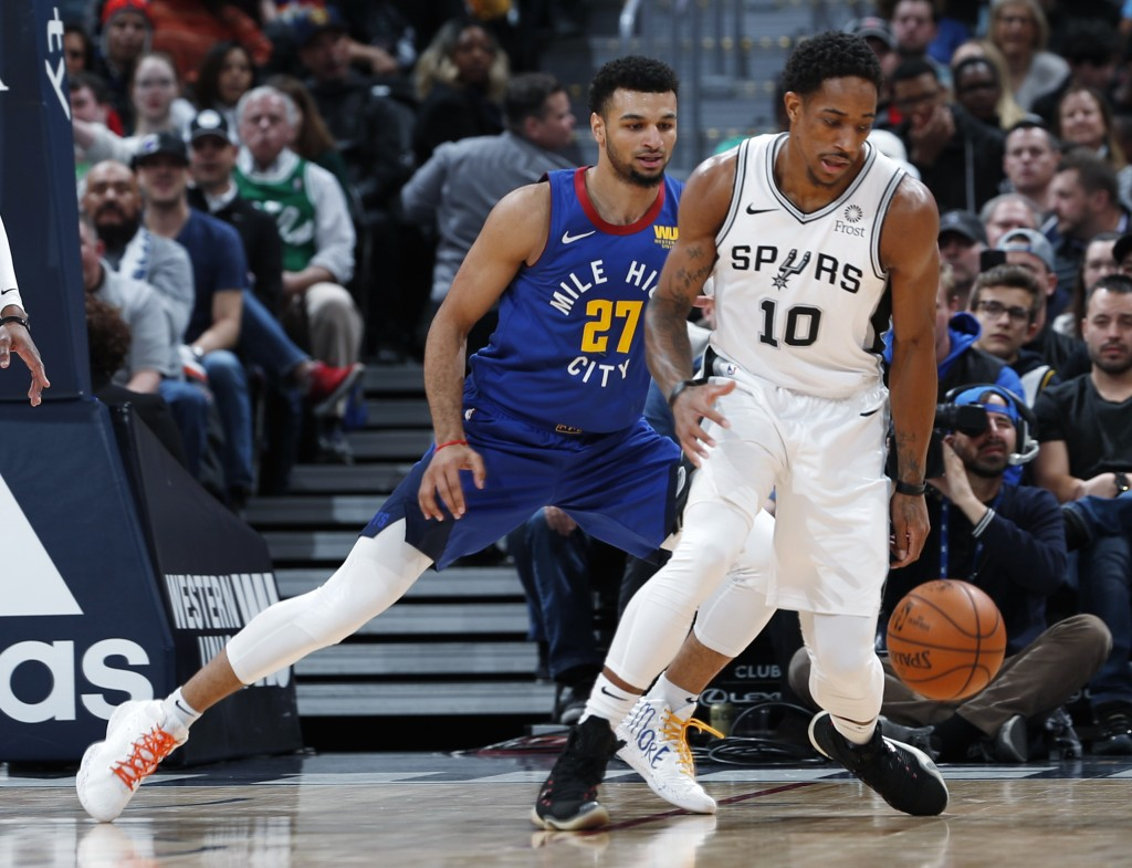 San Antonio Spurs guard DeMar DeRozan, front, pursues the ball with Denver Nuggets guard Jamal Murray in the first half of an NBA basketball gsm Frida...