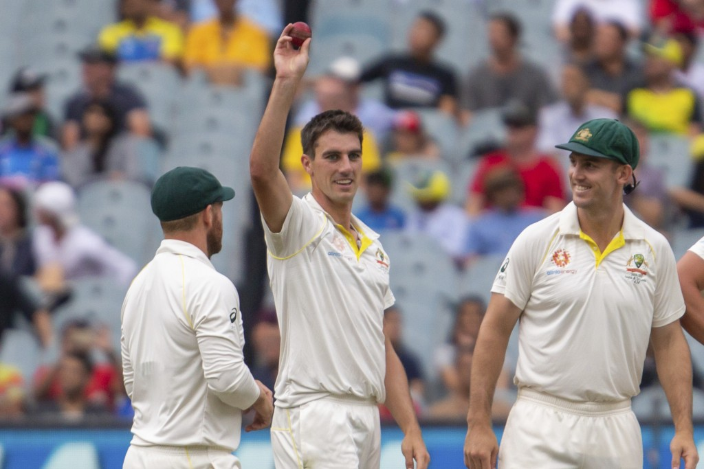Australia's Pat Cummins, center, raises the ball after getting his 5th wicket in the 2nd innings during play on day four of the third cricket test bet...