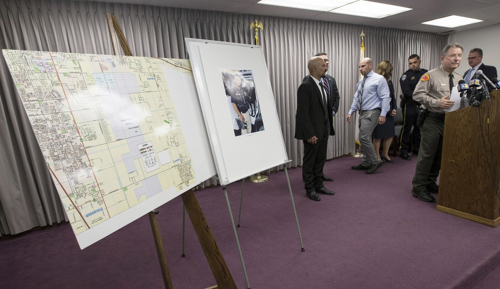 Kern County Sheriff Donny Youngblood, right, speaks at a news conference in Bakersfield, Calif., after suspect Gustavo Perez Arriaga surrendered and w...