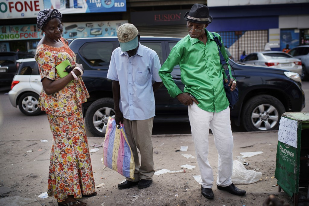 In this photograph taken Friday, Dec. 28, 2018, Kinshasa residents read newspaper headlines at a streetside newsstand in Kinshasa, Congo. Congolese pe...