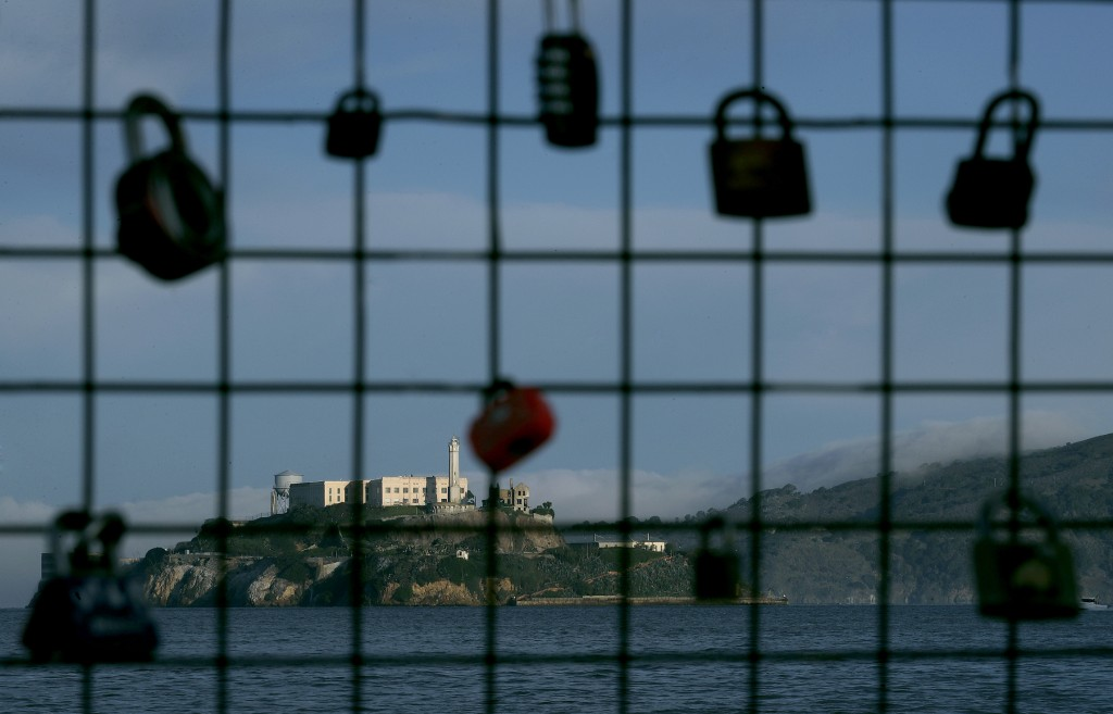 Alcatraz Island is shown behind a locks attached to a pier fence in San Francisco, Saturday, Dec. 22, 2018. A partial federal shutdown has been put in