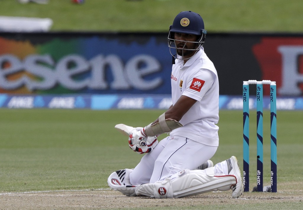 Sri Lanka's Dinesh Chandimal kneels on the pitch after avoiding a bouncer during play on day four of the second cricket test between New Zealand and S...