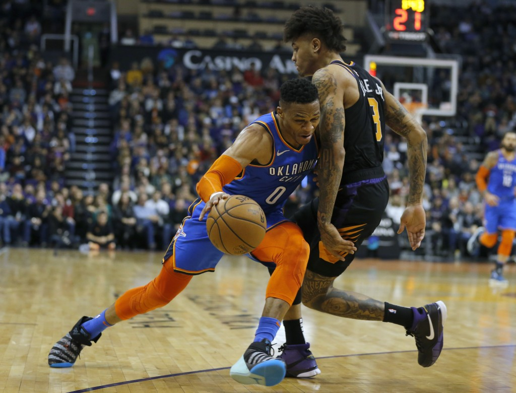 Oklahoma City Thunder guard Russell Westbrook (0) gets fouled by Phoenix Suns forward Kelly Oubre Jr in the first half during an NBA basketball game, ...