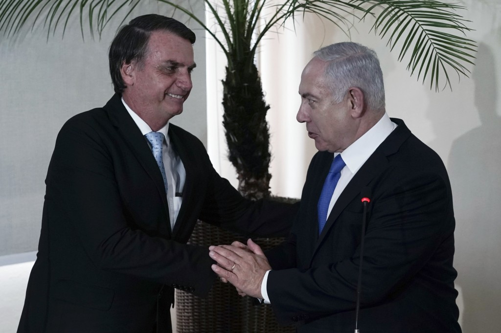Brazil's President-elect Jair Bolsonaro, left, and Israel's Prime Minister Benjamin Netanyahu shake hands during a joint statement at the military bas...