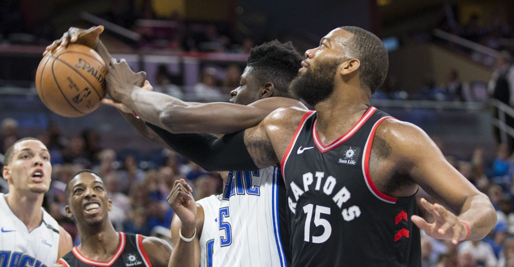 Orlando Magic center Mo Bamba (5) and Toronto Raptors center Greg Monroe (15) fight for the rebound during the first half of an NBA basketball game in...