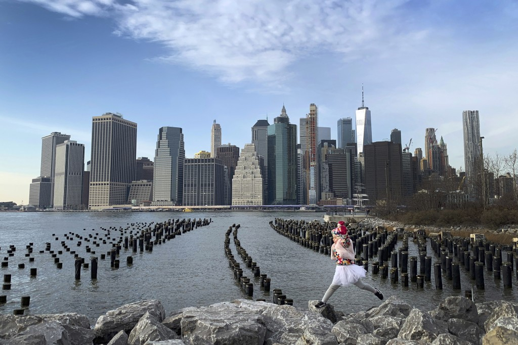 With downtown Manhattan in the background, a girl leaps across boulders forming a breakwater along the Brooklyn Bridge Park on Thursday Dec. 27, 2018,...