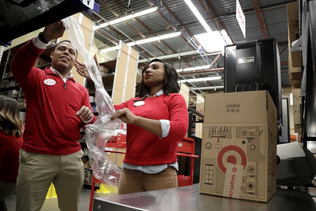 FILE - In this Nov. 16, 2018, file photo, employees demonstrate how air pillow machines work at a packaging station in the backroom of a Target store ...