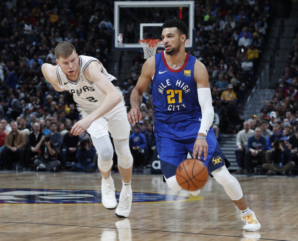 Denver Nuggets guard Jamal Murray, right, drives to the net past San Antonio Spurs forward Davis Bertans in the first half of an NBA basketball game F...