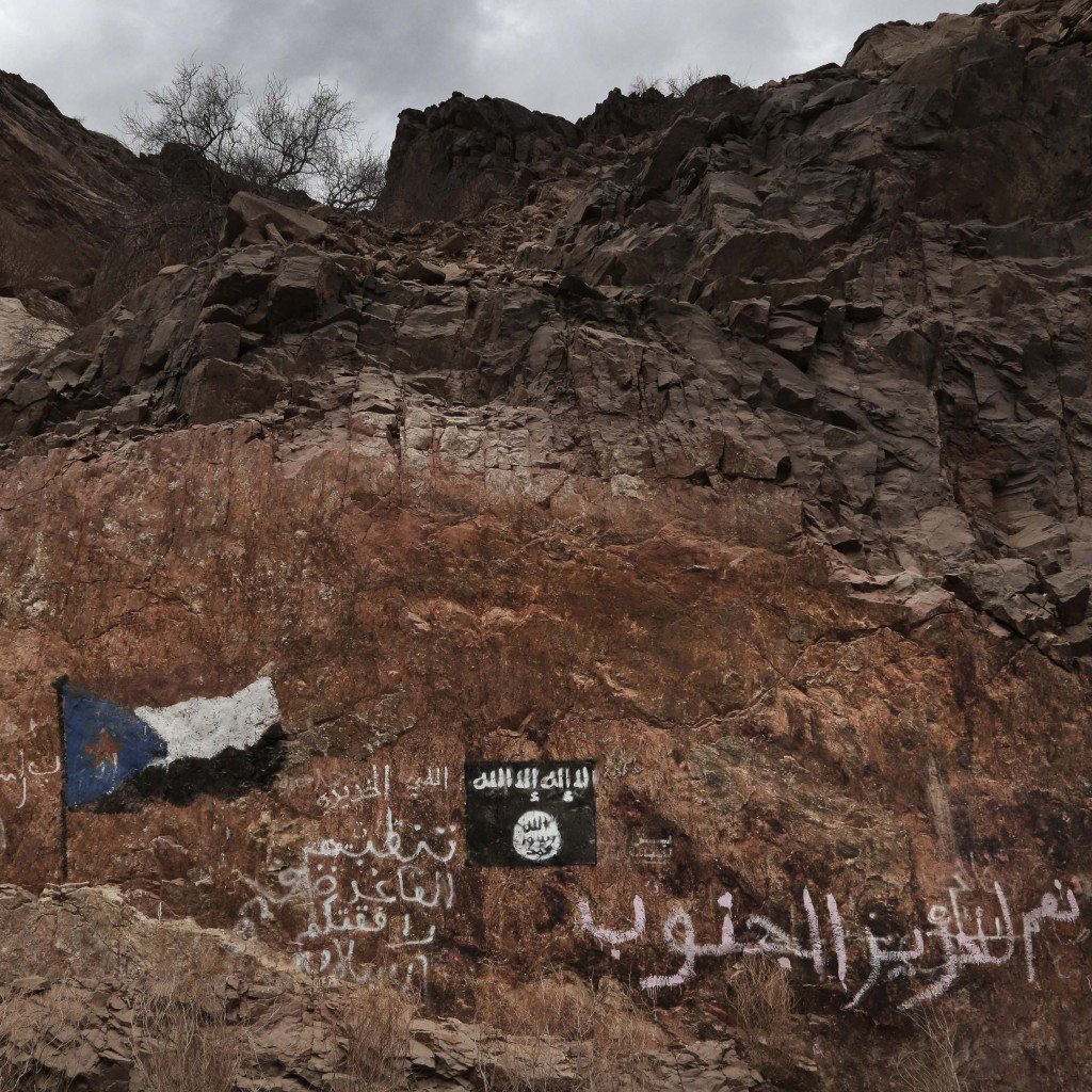 """This July 24, 2018 photo shows the al-Qaida flag painted on rocks near the southern flag with Arabic that reads, """"Yes to liberating the south,"""" and """"t..."""