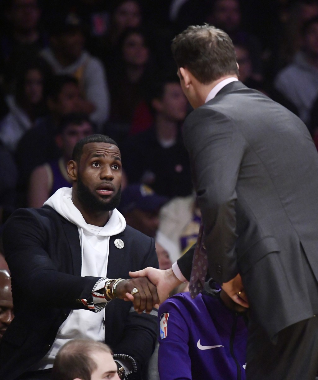 Los Angeles Lakers forward LeBron James, left, shakes hands with coach Luke Walton as they have a chat during the first half of an NBA basketball game...